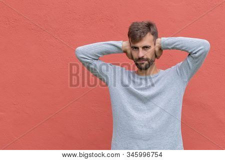 Bearded Man Covering Ears Ignoring Noise. Stressed Guy Plugging Ears With Palms. Male Covering Ears
