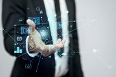 Close up of incognito businessman in suit standing in office. Selective focus of virtual projection of digital tactile charts screen, man holding in hand. Concept of high technologies, digitalization. poster