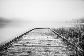 Misty Lake In The Middle Of The Forest And Old Wooden Bridge