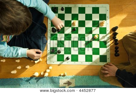 Young Boy Playing Chess On Floor