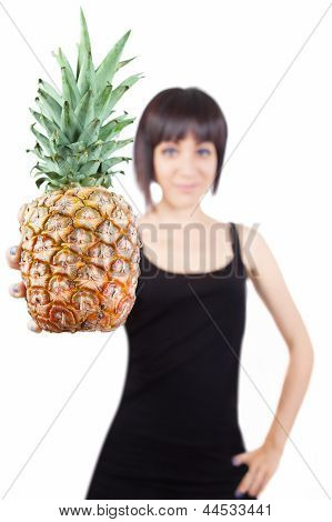 Girl (out Of Focus) Offering A Pineapple (in Focus)