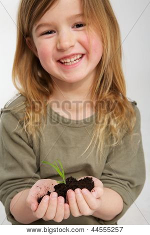 Smiling Girl With Plant Growing From Soil In Hands