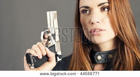 woman holding up her weapon in studio poster