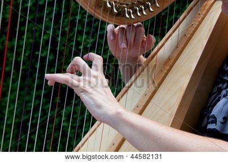 Hands strumming harp strings