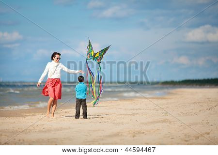 Young mather and her son playing with kite