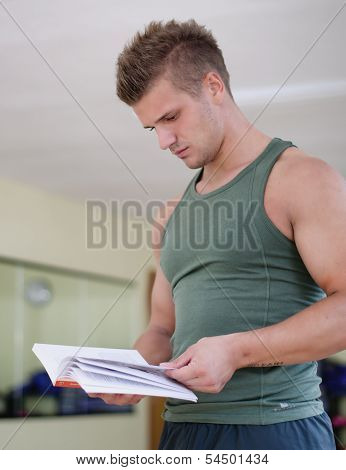 Handsome Young Man In Gym Reading Workout Book