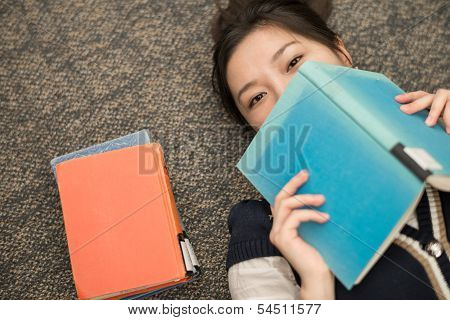 Student Laying On Carpet With Books