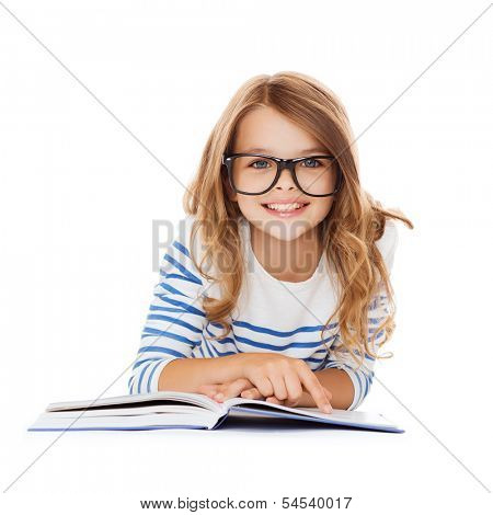 education and school concept - smiling little student girl with book and eyeglasses lying on the floor