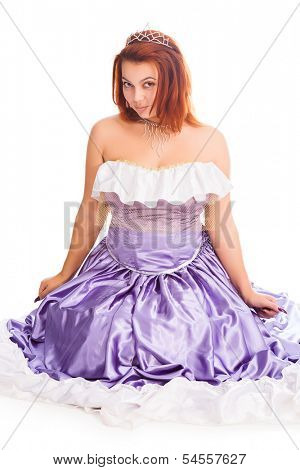 Young attractive sitting woman in long lilac-coloured ball dress and with diadem on head women isolated on white background