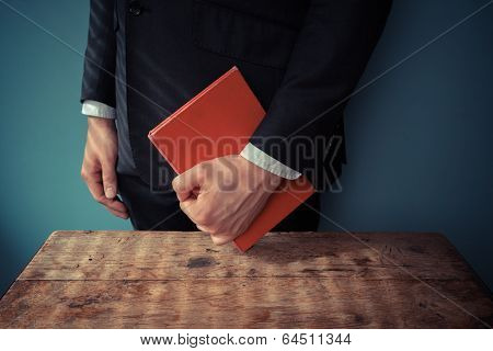 Man With Book At Desk
