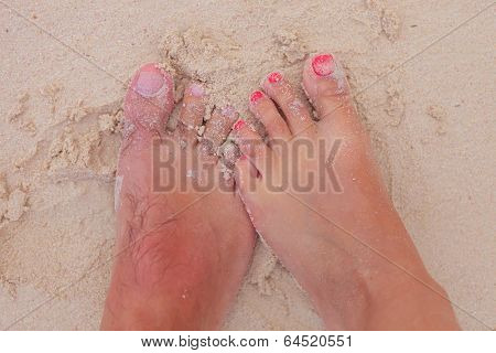 bare feet and toes of a young couple in wet sand