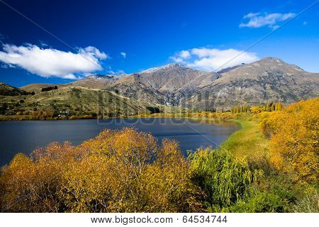 Lake surrounded by Autumn / Fall foliage with Mountain backdrop
