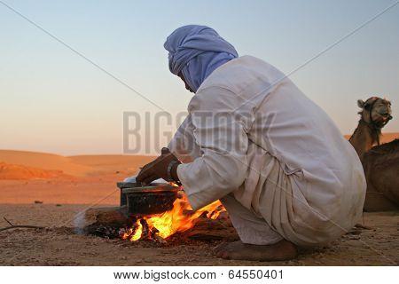Native arab bedouin making a dinner in middle of the desert in Egypt