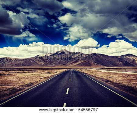Vintage retro effect filtered hipster style travel image of Travel forward concept background - road on plains in Himalayas with mountains and dramatic clouds. Manali-Leh road, Ladakh, India