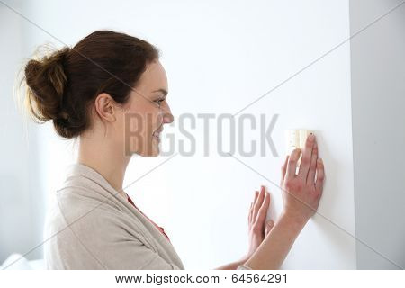 Woman programming temperature inside home