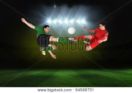 Football players tackling for the ball against football pitch under spotlights poster
