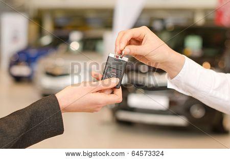 Female Hand Getting Modern Car Key On Several Car Background
