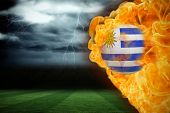 Composite image of fire surrounding uruguay flag football against football pitch under stormy sky poster
