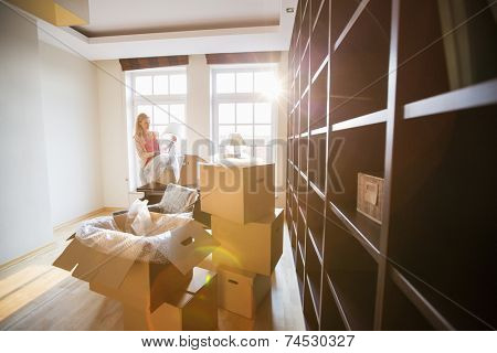 Woman unpacking lamp from moving box at new house
