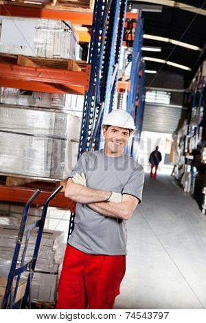 Portrait of smiling warehouse worker with handtruck at warehouse