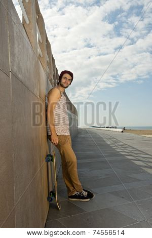 Young skater boy leaning against a granite wall of an urban boardwalk urban setting along the seashore with a skateboard next to him