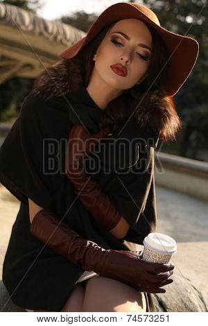 Beautiful Girl In Elegant Coat And Hat Drinking Coffee At Park
