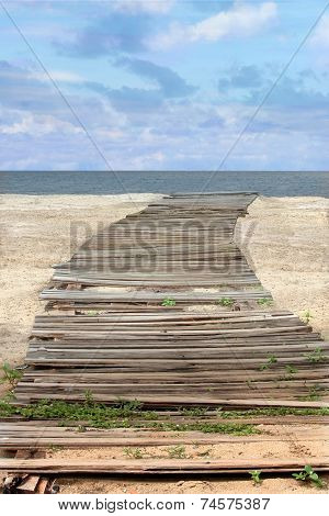 Vintage Wooden Plank Path on Sandy Beach Leading to Sea with vertical orientation