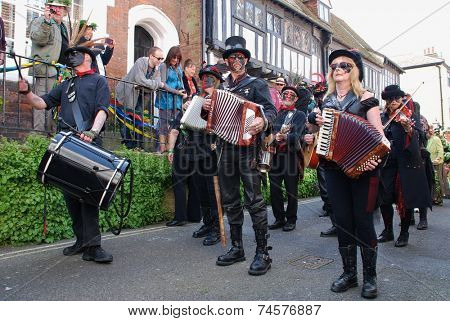 HASTINGS, ENGLAND - MAY 5, 2014: Black faced musicians perform at the parade through the Old Town during the annual Jack In The Green festival. The event is held on the May Day public holiday.