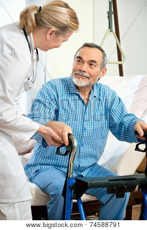 doctor or nurse helps a senior patient to get up in hospital
