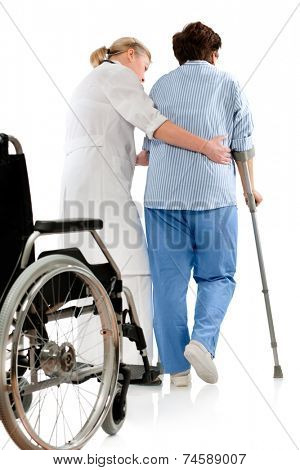 nurse helps a senior woman on crutches
