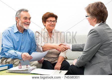 Seniors ouple meeting with financial adviser, handshake