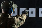 Man shooting with gun at a target in shooting range poster