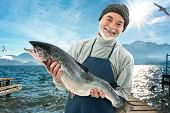 Fisher holding a big atlantic salmon fish in the fishing harbor poster