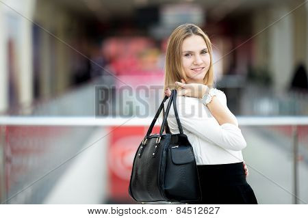 Young Female Model In Stylish Outfit Holding Handbag