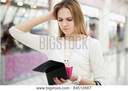 Confused Young Woman Checking Her Purse After Spending Too Much In Shop