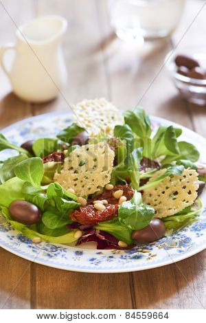 Salad with parmesan chips, dried tomatoes and olives