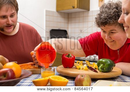 Mentally Disabled Woman And Two Caretakers Cooking Together