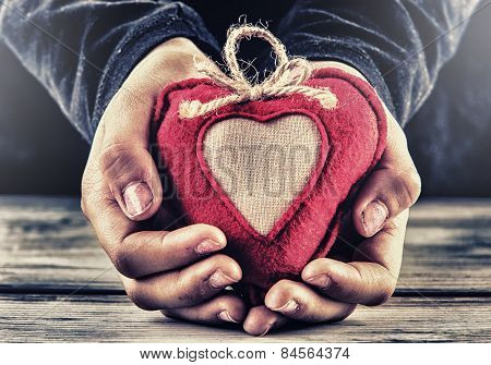 Red canvas valentine heart in the hands of a child. Heart gift as a token of love.