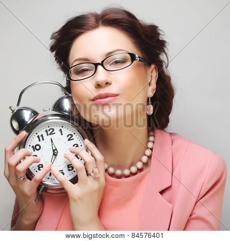 Young fun businesswoman with alarmclock