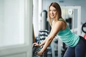 Beautiful young woman blonde with gray eyes, with a perfect figure, fitness trainer, dressed in a blue sports jersey is in the gym, choose silver dumbbells for exercise. poster
