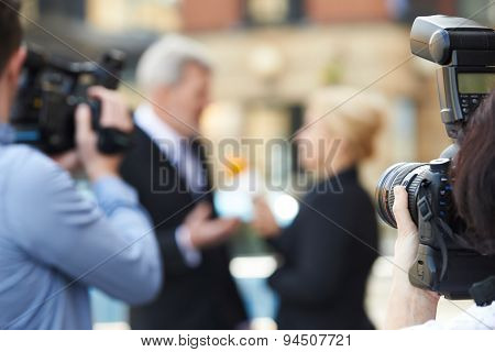 Photographer Taking Pictures Of Female Journalist Interviewing Businessman poster
