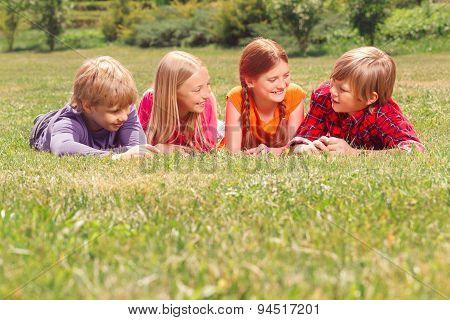 Upbeat children lying on grass in raw