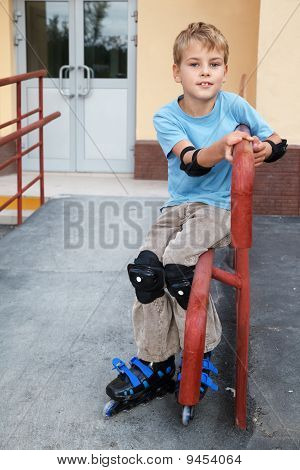 Boy in rollerblades knee and elbow pads sitting on the railing in front of house.