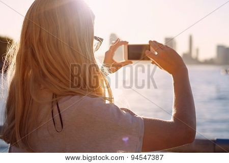 Closeup of blonde girl in glasses taking picture of city bay with mobile phone on sunset. Focus on glasses