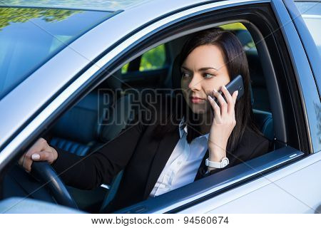 Successful Business Woman Talking On Smartphone In Her Car