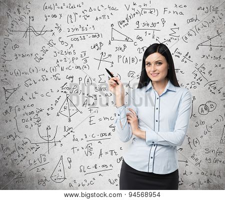 Portrait Of Smiling Woman Who Points Out Complicated Math Calculations. Math Formulas Are Written On