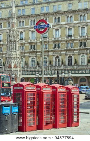 LONDON, UK - JUNE 15: Four traditional red phone booth with underground sign in front of Charing Cross station. June 15, 2015 in London.