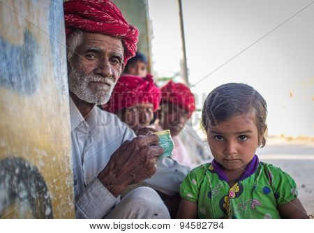 GODWAR REGION, INDIA - 12 FEBRUARY 2015: Rabari tribesman with other members while granddaughter stands next to him. Rabari or Rewari are an Indian community in the state of Gujarat.