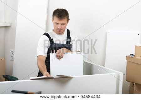 Man Dressed In Workers' Overall Assembing Furniture