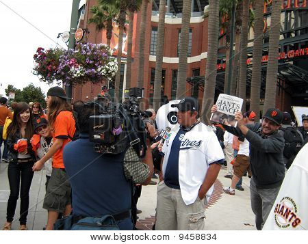 Padres Fan Interviewed By Newsreporter With Giants Fans Celebrating Winning Division Behind Him